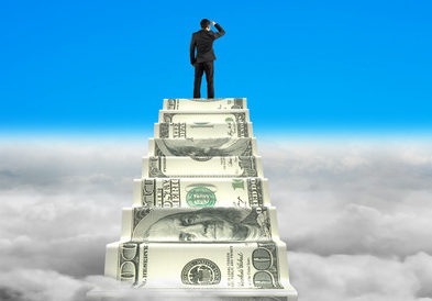 businessman reaching the top of money stairs