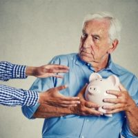 elderly man clutching piggy bank